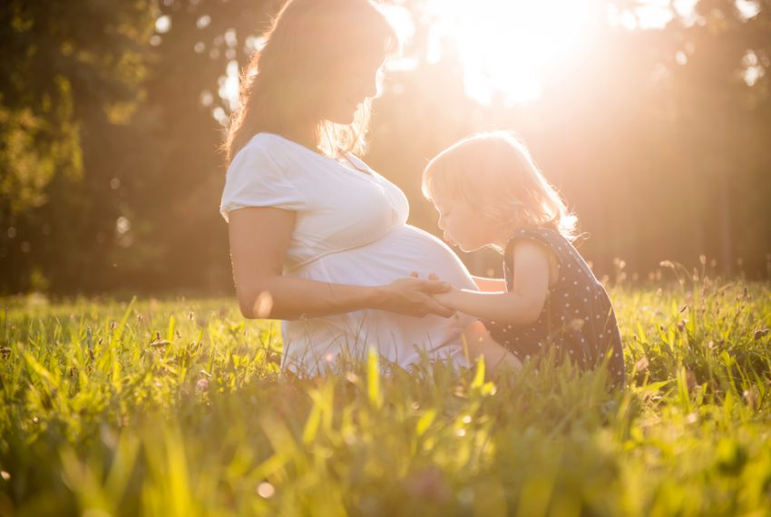 Young child kissing a pregnant woman's stomach in a field