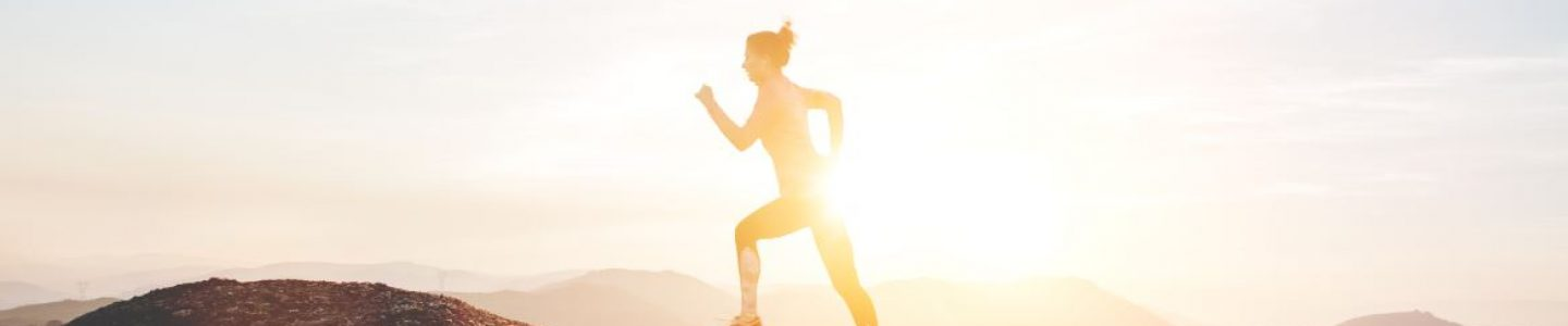 Woman running on a mountain at sunset